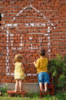 Kinder malen Hauszeichnung an eine Wand