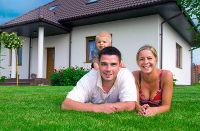 Familie vor ihrem Eigenheim