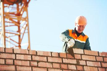 Handwerker mit Arbeiten vor einem Haus