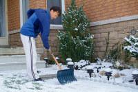Mann schaufelt Schnee im Winter
