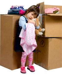 Trauriges Kind vor Umzugskartons
