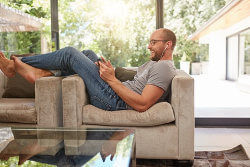 Mann liegt entspannt auf Couch und berechnet Darlehen