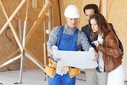 paar mit Bauleiter und Bauplan auf einer Hausbaustelle