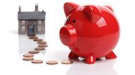Sparschwein auf einem Weg aus Pfennigen und Cents vor einem Haus
