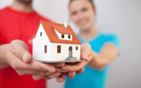 Paar zeigt durch Baufinanzierung realisiertes Haus