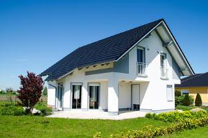 Bild zeigt ein großes, weißes Einfamilienhaus im Sonnenschein