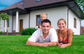 Eine Familie liegt im Gras vor ihrem Haus