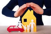 Hände werden schützend über ein Haus und eine Familie aus Papier gehalten