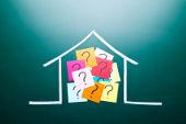 In einem gemalten Haus befinden sich mehrere bunte Post-Its, auf denen Fragezeichen zu sehen sind