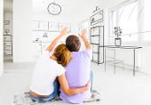 Paar sitzt in einem leeren Zimmer und zeichnet seine Traumeinrichtung