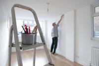 Bild zeigt eine Leiter, im Hintergrund ein Mann beim Heimwerken