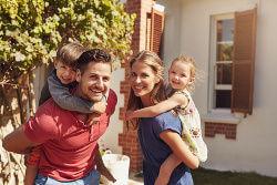 Glückliche Familie vor schönem Haus