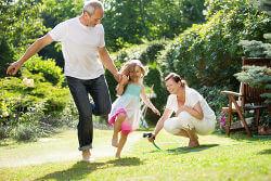 Glückliche Familie spielt im Garten