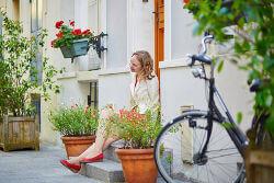 Junge Frau sitzt lächelnd auf der Treppe vor ihrem Haus