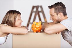 Junges Paar mit Sparschwein in der eigenen Wohnung