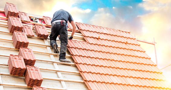 Ein Handwerker verlegt Dachziegel